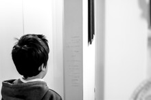 Rear View Of Boy Reading Text Written On Wall