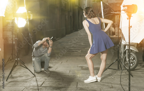 Leinwand Poster Photographer using professional camera and light equipment for taking pictures o