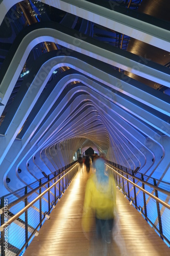Blurred Motion Of People On Covered Bridge At Night