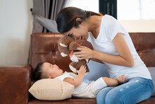 Woman Playing With Son On Sofa At Home