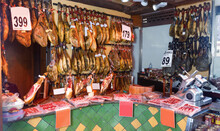Assortment Of Traditional Delicious Spanish Meat Shop With Dangling Legs Jamon And Packings Of Sliced Ham