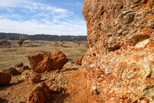 View Of Red Conglomerate Rock With Forested Hill And Houses In The Background From Rattlesnake Bar In Newcastle California