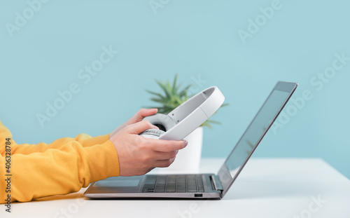 Side view of slim laptop and hands with wireless headphones on grey desk. Blue background. Distant learning. working from home, online courses or support. Audio podcast. vlogger or blogger banner
