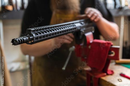 Fotografia Gunsmith working on an 300 Blackout AR rifle upper receiver in a vise at a gun s