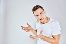 Emotional Man Gestures With His Hands Displeasure White T-shirt Light Background