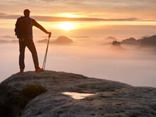 Man Silhouette With Poles In Hand. Sunny Spring Daybreak And  Guide Stay On  Cliff Of Mountain