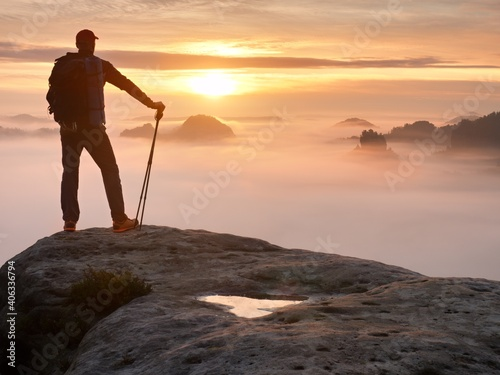 Obraz Man Silhouette With Poles In Hand. Sunny Spring Daybreak And  Guide Stay On  Cliff Of Mountain - fototapety do salonu