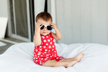 Cute Baby Girl Wearing Sunglasses While Sitting On Bed At Home