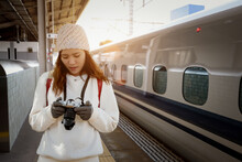 Asian Young Female Photographer Traveling Alone Holds A Camera At A Train Station In Japan During Winter.