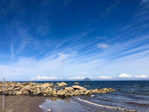 Fotografiet Scenic View Of Sea Against Blue Sky And Ailsa Craig