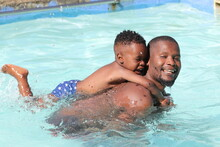 Father And Son Enjoying In Swimming Pool