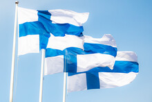 Three Finnish National Flags On The Wind Against The Blue Sky