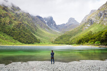 Person Stand In Front Of Emily Peak In Lake Mackenzie At The Famous Routeburn Track In Summer, Fjordland National Park, Southland, New Zealand