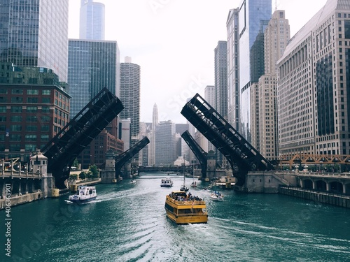Photo Ferries Sailing On River By Modern Buildings In City Against Clear Sky