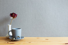 Coffee Cup With Dry Rose On Wooden Table. Gray Background