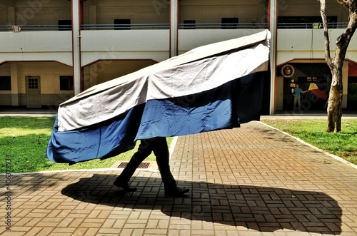 Canvas Man Carrying Fabric Material Against Built Structure