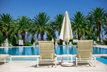 Two White Plastic Sun Loungers And Parasol Stand Near The Pool With Turquoise Water On The Pallm Trees Background