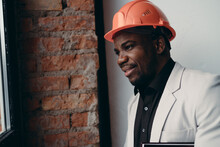 Portrait Of An African American Man Standing In A Construction Helmet And Holding A Folder In His Hands