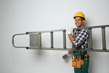 Professional Builder Carrying Metal Ladder On Light Background