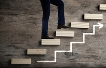 Businessman Walking Up Stairs Against Wooden Background, Closeup. Career Ladder Concept