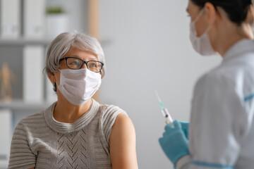 Panel Szklany Siatkówka Doctor giving a senior woman vaccination
