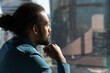 Close up of pensive African American man look in window distance thinking or pondering of future career opportunities. Thoughtful ethnic male make decision or plan. Business vision concept.