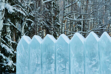 A Fence Made Of Ice Boards On The Background Of Frozen Firs And Birches In The Snow. Beautiful Winter Landscape With A Copy Of The Space