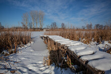 Snow-covered Wooden Bridges Surrounded By Reeds On A Frozen Pond.