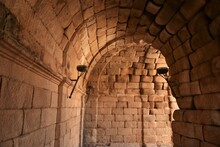 Elegant And Pleasantly Lit Pink Sandstone Tunnel Lined By Rustic Torch Holders Leading Into The Famous Roman Theater Of Merida
