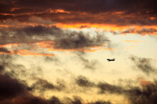 A Commercial Airline Plane Descends Through Clouds At Sunset.