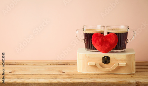 Valentine's Day concept with couple of coffee cups and heart shape on wooden table over pink background © maglara