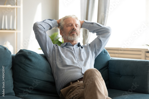 Obraz Relaxed smiling middle aged mature grey-haired man resting with closed eyes on cozy couch, enjoying stress free sweet tranquil weekend time alone indoors, daydreaming or meditating alone at home. - fototapety do salonu