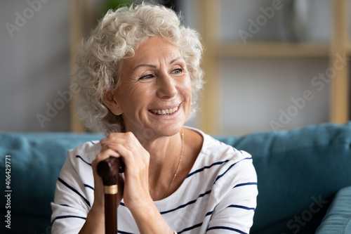 Canvas Head shot smiling mature grandmother with walking disability looking in distance, daydreaming or planning future