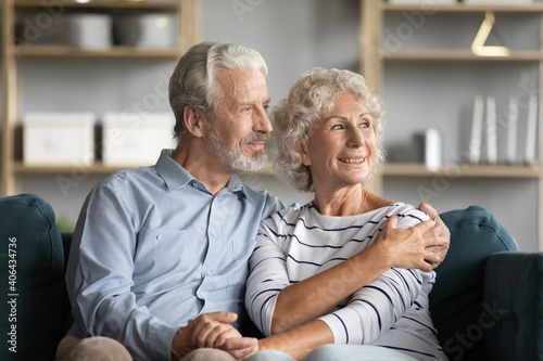 Foto Dreamy middle aged senior loving retired family couple looking in distance, planning common future or recollecting memories, enjoying peaceful moment relaxing together on cozy sofa in living room