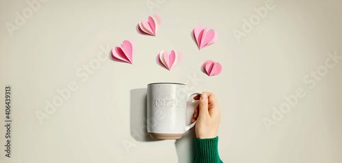 Obraz Female hand holding a mug with paper craft hearts - flat lay - fototapety do salonu