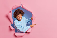 Happy Surprised Dark Skinned Woman Peeps Through Hole In Paper Points At Blank Space Advertises Item Wears Blue Sweatshirt Expresses Happiness Shows You Way. People And Advertisement Concept