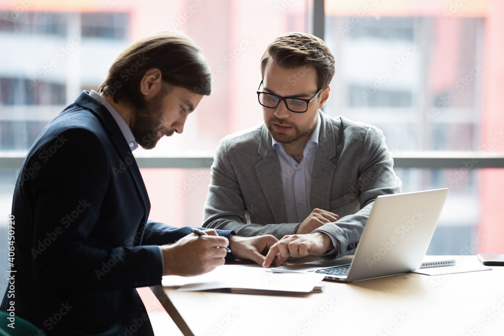 Fototapeta Focused young businessman signing agreement with skilled lawyer in eyeglasses. Concentrated financial advisor showing place for signature on paper contract document to male client at meeting in office - obraz na płótnie