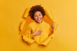 Leinwandbild Motiv Happy curly haired young woman feels sincere and happy smiles broadly keeps hand on chest dressed in yellow sweater poses through ripped hole has good mood. People emotions and feelings concept