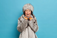 Sad Frustrated Young Asian Woman Wears Fur Hat And Coat Cries Unhappily Dresses For Cold Weather Expresses Negative Emotions Isolated Over Blue Backgrund. Northern Inhabitant Adapted To Frost