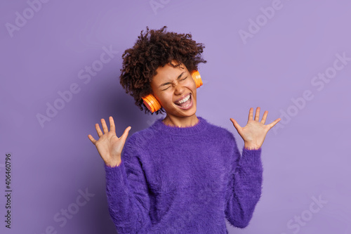 Overjoyed dark skinned woman sings song loudly raises palms has overemotive expression wears headphones on ears for listening music dressed in casual jumper isolated over purple studio background