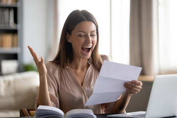 Close up overjoyed young woman reading good news in letter, holding paper sheet, sitting at desk with laptop, happy amazed female celebrating job promotion or great exam results, money refund