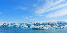 Ice Winter Panoramic View On Glacial Lake Jokulsarlon Lagoon Iceland, Amazing Ice Floes Surreal Iceberg Snow Cupped Mountain Blue Sparkling Ice, Awesome Icelandic Nature, White Polar Arctic Landscape.