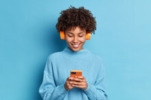 Smiling Teenager With Afro Hair Listens Favorite Music Track Holds Mobile Phone Downloads Song To Her Playlist Dressed In Casual Jumper Isolated Over Blue Background. People Hobby Technology