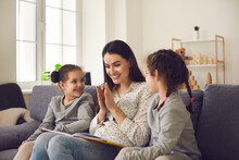 Caring Smiling Mom Reading A Book With Her Two Little Daughters Sitting On The Couch At Home. Mom Or Babysitter Play And Have Fun Telling A Fairy Tale To The Twin Sisters. Family Activities Concept.