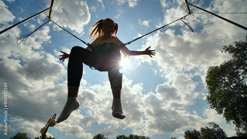 Photographie Teenage girl silhouette jumping on the trampoline bungee jumping.
