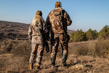 A Man And A Woman In Hunting Suits And With Rifles Stand On The Hill, The Hunters Stand With Their Backs On The Top Of The Hill