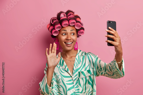 Positive dark skinned woman with hair rollers on head smiles broadly waves palm at smartphone camera wears silk dressing gown spends free time at home caring about her appearance makes video call