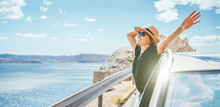 Cheerful Woman Portrait Enjoying The Seaside Road Trip. Dressed A Black Dress With Straw Hat And Sunglasses She Wide Opened Arms And Shining With Happiness. Summer Vacation Traveling By Auto Concept.