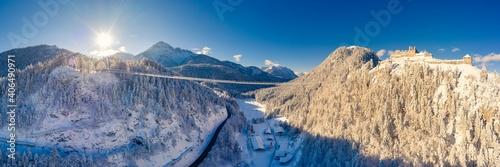 wiszący most dla pieszych nad pustelnią i ruiną Ehrenberg w reutte w śnieżną zimę z promieniami słońca