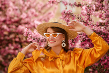 Happy Smiling Woman Wearing Trendy  Straw Hat, Yellow Satin Blouse, White Cat Eye Sunglasses, Big Earrings, Posing In Street Near Pink Spring Blossom Trees. Copy, Empty Space For Text